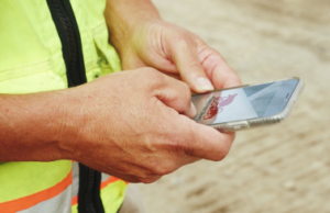 Man holding phone looking at DirectConcrete app